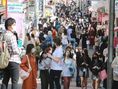 People wearing face masks to protect against the spread of the coronavirus walk on a street in Tokyo (AP)