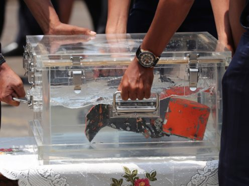 Investigators carry a box containing the cockpit voice recorder (AP)