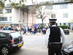 A police officer outside Pimlico Academy in London where pupils staged a walkout (Aaron Chown/PA)