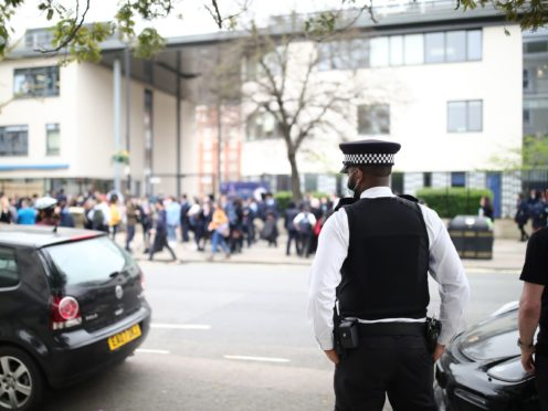 A police officer watches the demonstration outside Pimlico Academy in London (Aaron Chown, PA)