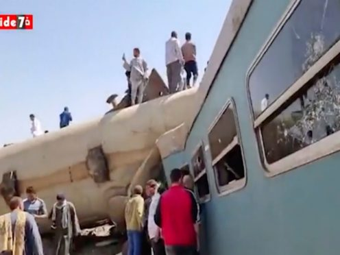 This image provided by Youm7 shows crowds of people gathered around mangled train carriages at the scene of a train accident in southern Egypt, Friday, March 26, 2021. Two trains collided apparently after someone activated the emergency brakes, killing several people and leaving others injured, Egyptian authorities said. (Youm7 via AP)