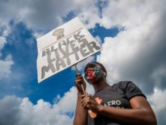 A woman holds a banner during a Black Lives Matter protest rally in Leeds (Danny Lawson/PA)