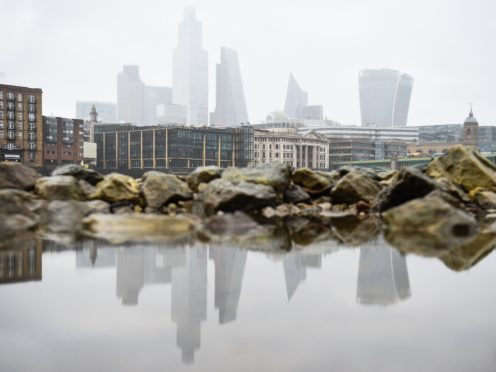 The City of London skyline is reflected in a puddle on the banks of the River Thames in London (Kirsty O'Connor/PA)