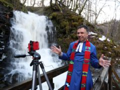 Rev Neil Glover, the minister at Aberfeldy Church in Perthshire, records a sermon beside the Birks of Aberfeldy waterfall (Andrew Milligan/PA)