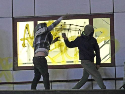 Protesters on a roof throw objects down at police outside Bridewell Police Station (Andrew Matthews/PA)