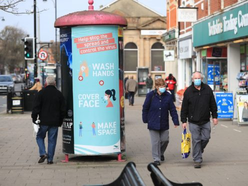 People wearing face masks walk past a coronavirus advice sign in Skegness, Lincolnshire (Mike Egerton/PA)