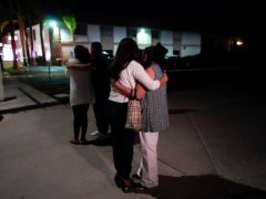 People comfort each other near the building where the shooting took place (Jae C. Hong/AP)