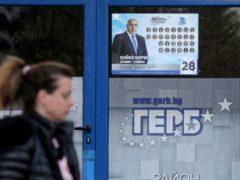 A woman passes by a poster depicting Bulgarian prime minister Boyko Borisso (Valentina Petrova/AP)
