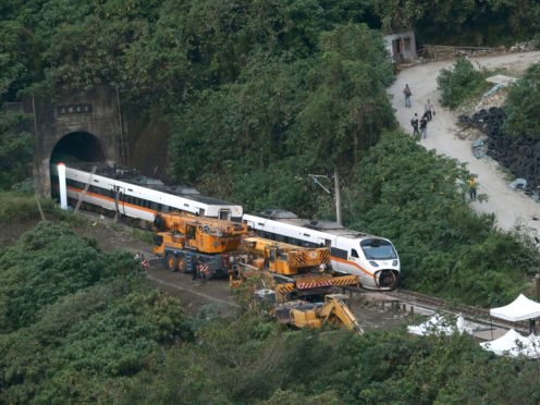 Rescue workers remove part of the derailed train (Chiang Ying-ying/AP)