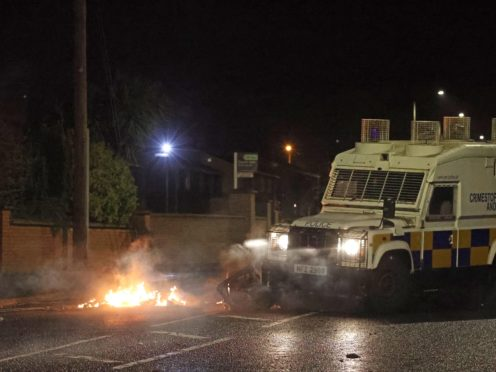 The PSNI moving a bin which was set alight on North Road in Carrickfergus near Belfast following sporadic outbursts of disorder. Picture date: Sunday April 4, 2021.