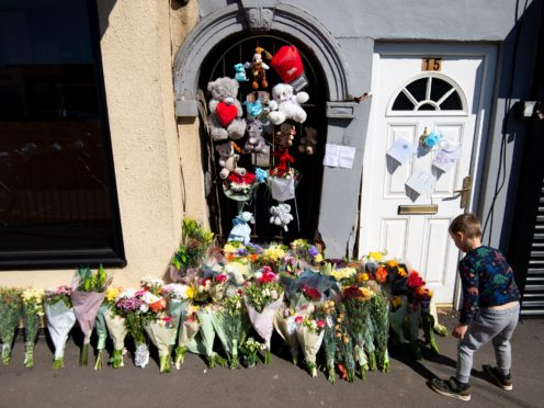 A boy lays flowers at the scene on High Street, Brownhills, near Walsall in the West Midlands (Jacob King/PA)