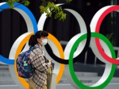 A woman wearing a protective mask walks in front of the Olympic Rings in Tokyo (Eugene Hoshiko/AP)