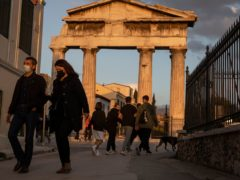People wearing face masks walk in front of the Gate of the Ancient Roman Agora in the Plaka district of Athens (Petros Giannakouris/AP)