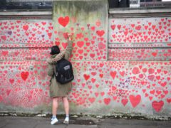 A woman writes in a heart on the National Covid Memorial Wall on the Embankment in London (Victoria Jones/PA)
