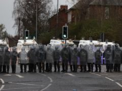 PSNI officers with riot shields line the Springfield road, during further unrest in Belfast (Liam McBurney/PA)