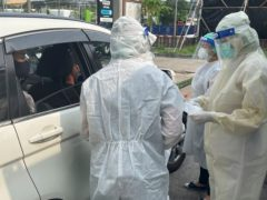 Medical workers carry out swab tests at a drive-through Covid testing facility outside a hospital in Nonthaburi, Thailand (Kiko Rosario/AP)