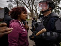 A person confronts a police officer near the site where a family said a man was shot and killed by local law enforcement in Brooklyn Centre, Minnesota (Christian Monterrosa/AP)