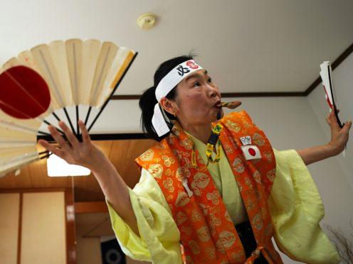 Olympic fan Kyoko Ishikawa shows her cheering at her home in Tokyo (Eugene Hoshiko/AP)