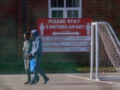 Two men walk past signs recently erected at Napier Barracks in Folkestone, Kent (PA)