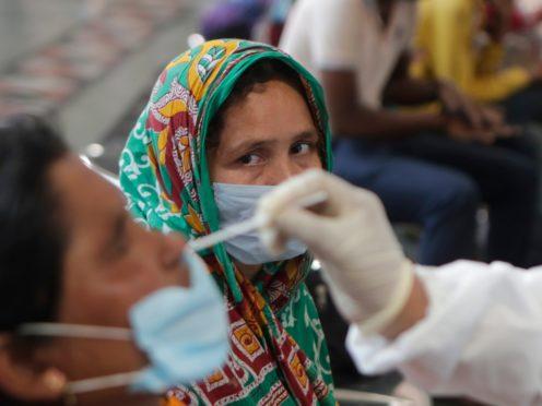 A health worker collects a swab sample at Chhatrapati Shivaji Maharaj Terminus in Mumbai (AP)