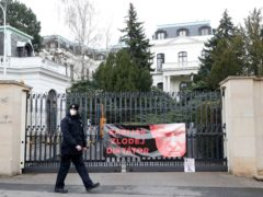 A policeman walks by a poster attached by protesters to a gate of the Russian embassy in Prague (Petr David Josek/AP)