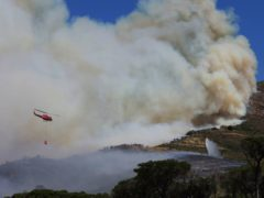 A helicopter drops water over a fire at Rhodes Memorial on Table Mountain, Cape Town (Nardus Engelbrecht/AP)