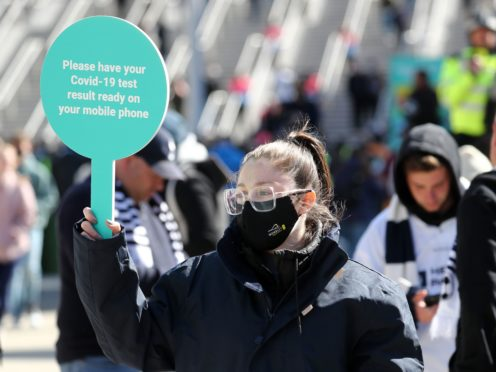 A steward in a mask outside Wembley stadium asks fans for Covid-19 test results as a condition of entry ahead of the Carabao Cup Final (Gareth Fuller/PA)