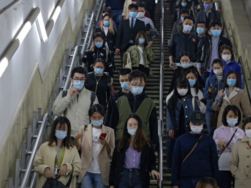 People on an escalator in Beijing (Andy Wong/AP)