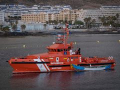 A wooden boat is towed by a Spanish Maritime Rescue Service ship (Andres Gutierrez/AP)