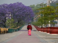 A Nepalese woman walks on a deserted street during the first day of lockdown in Kathmandu, Nepal (Niranjan Shrestha/AP)