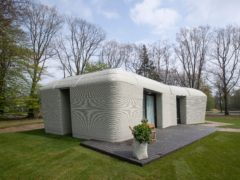 Exterior view showing the printer layers in the walls of the 3D-printed 94-square meters (1,011-square feet) two-bedroom bungalow resembling a boulder with windows in Eindhoven, Netherlands, Friday, April 30, 2021. The fluid, curving lines of its gray walls look natural. But they are actually at the cutting edge of housing construction in the Netherlands and around the world. They were 3D printed at a nearby factory. (AP Photo/Peter Dejong)