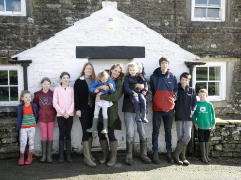 Contributors Amanda and Clive Owen with their children Annas, Violet, Edith, Raven, Clemmy, Nancy, Reuben, Miles, and Sidney outside on Ravenseat Farm (Renegade Pictures)