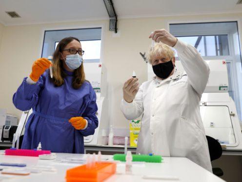 Prime Minister Boris Johnson looks at samples during a visit to Porton Down (PA)
