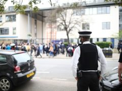 A police officer outside Pimlico Academy School, west London (PA)