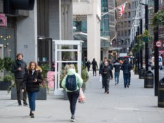 People pass shops and offices on a street in central London (Dominic Lipinski/PA)
