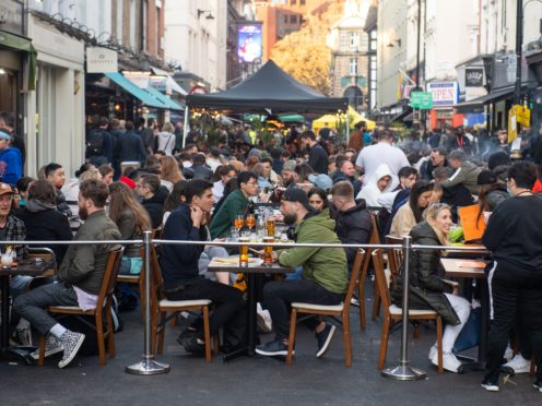 People eat and drink at outside tables in Soho, central London (Dominic Lipinski/PA)