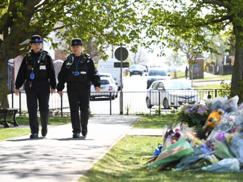 Police Community Support Officers walk past floral tributes in a park in Aylesham village (PA)