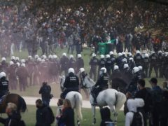 """Police attempt to disperse gatherers at the Bois de la Cambre park during a party called """"La Boum 2"""" in Brussels, Saturday, May 1, 2021. Police put on extra patrols Saturday to monitor the gathering which is being held in defiance of Belgium's current COVID-19 regulations. (AP Photo/Olivier Matthys)"""
