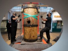 Workmen install a section of the original wooden foremast from HMS Victory with a hole in the middle made by a cannon ball during the Battle of Trafalgar (Andrew Matthews/PA)