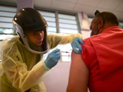 A healthcare worker injects a man with a dose of the Moderna Covid-19 vaccine in Puerto Rico (Carlos Giusti/AP)