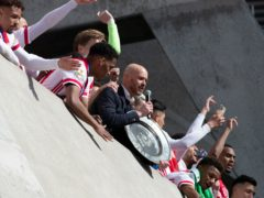 Ajax coach Erik ten Hag and players hold the trophy as they celebrate clinching the Dutch Eredivisie Premier League title at the Johan Cruyff ArenA in Amsterdam, Netherlands (Peter Dejong/AP)