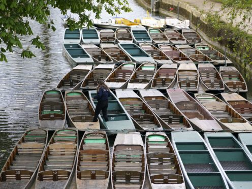 A member of staff maintains punts in Oxford, following the further easing of lockdown restrictions in England (Steve Parsons/PA)