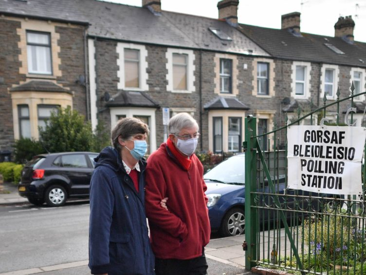 First Minister Mark Drakeford and his wife, Clare Drakeford, arriving at St Catherine's church hall polling station to cast their votes (PA)