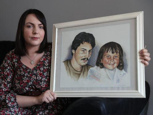 Charlene Smyth, holds a painting of herself with her father Charlie McGrillen, who was killed by the UFF in 1988 (Brian Lawless/PA)