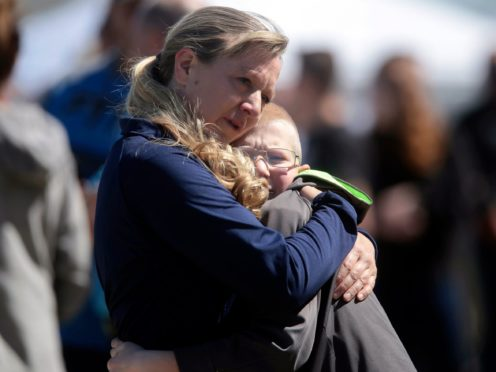 People embrace after a school shooting at Rigby Middle School (John Roark/The Idaho Post-Register via AP)