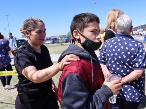 Adela Rodriguez, left, walks with her son, Yandel Rodriguez, 12, at the school where pupils were shot (Natalie Behring/AP)