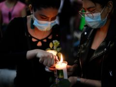 A woman lights a candle during a march demanding justice for the people who died in Monday's subway collapse, in Mexico City's south side (Eduardo Verdugo/AP)