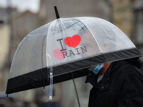 A man walks past the shops in Porthcawl, Wales, during a heavy downpour. Picture date: Saturday May 8, 2021.