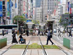 People wearing face masks make their way in Hiroshima, western Japan (Shingo Nishizume/Kyodo News via AP)