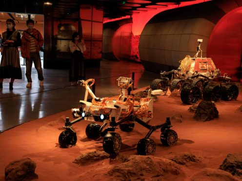 Visitors pass by an exhibition depicting rovers on Mars in Beijing (AP)